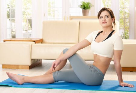 Girl doing exercise on polyfoam mat in living room. photo