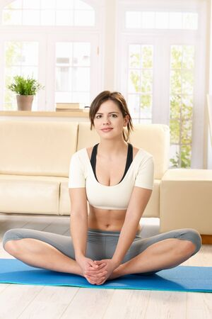 Pretty girl doing stretching exercise on blue polyfoam mat at home. Stock Photo - 7263667