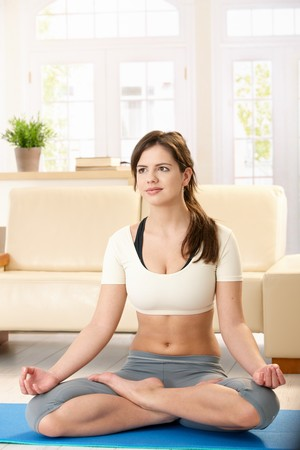 Pretty girl meditating in lotus posture sitting on polyfoam mat in living room. photo