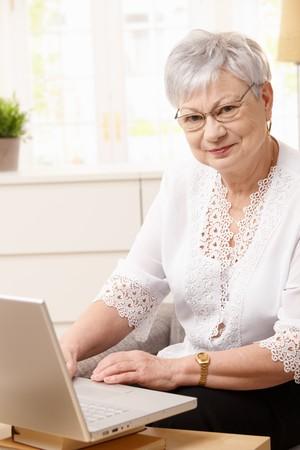 Senior woman using laptop computer at home, looking at camera smiling. photo