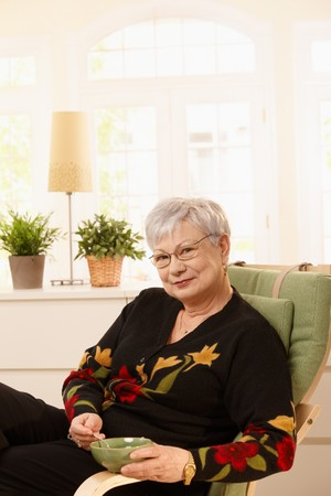 Portrait of senior lady having tea at home, sitting in armchair, smiling at camera. photo