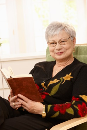 Portrait of elderly woman sitting in armchair with book in hand, smiling at camera. photo
