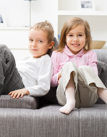 Portrait of happy little brother and sister sitting together on couch at home, smiling.  photo