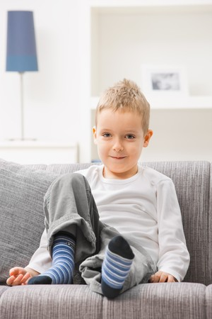 Portrait of happy little boy wearing white t-shirt, sitting at couch, looking at camera, smiling. Stock Photo