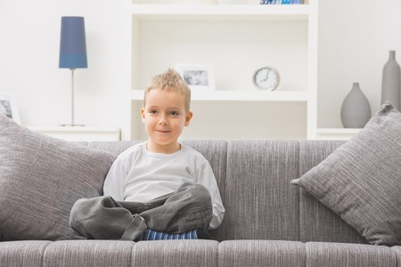 Portrait of little boy wearing white t-shirt, sitting at couch, looking at camera, smiling. photo
