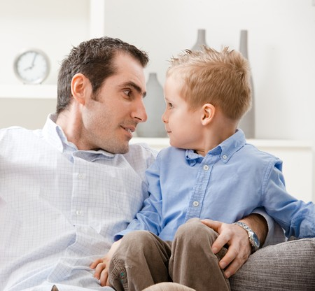Little boy and his father sitting on couch, looking into each others eyes. photo