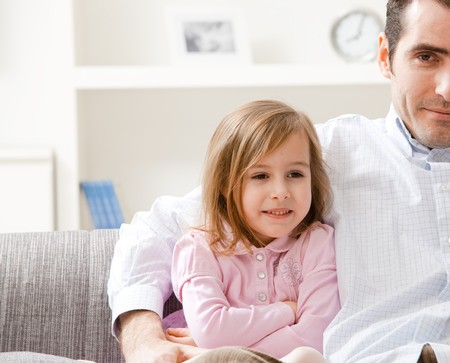 Little girl wearing pink dress sitting on couch with her father, smiling. photo