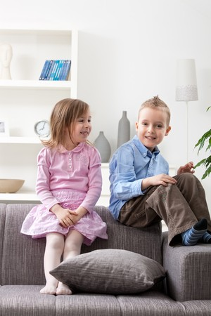 Portrait of happy little brother and sister sitting together on couch, smiling.  photo