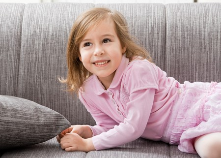 Happy little girl in pink dress, lying on couch, smiling. photo