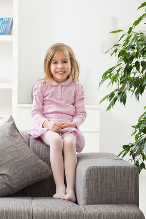 Portrait of happy little girl in pink dress, sitting on couch, smiling. photo