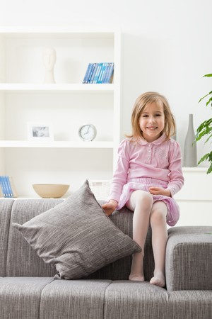 Portrait of happy little girl in pink dress, sitting on couch, smiling. Stock Photo - 7273380