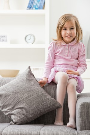 only 1 girl: Portrait of happy little girl in pink dress, sitting on couch, smiling. Stock Photo