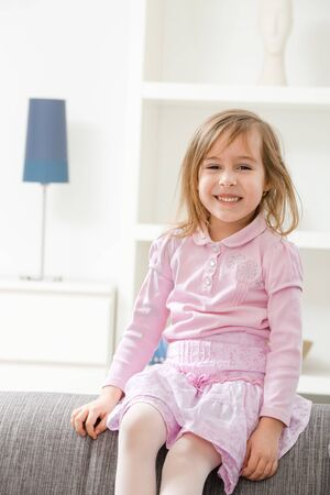 little girl smiling: Portrait of happy little girl in pink dress, sitting on couch, smiling. Stock Photo