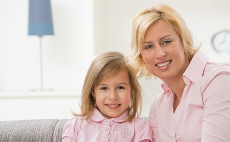 Portrait of blonde little girl and mother wearing pink, smiling. photo
