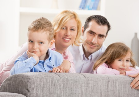 Portrait of happy couple and their two children, smiling. Selective focus on boy. Stock Photo - 7273270