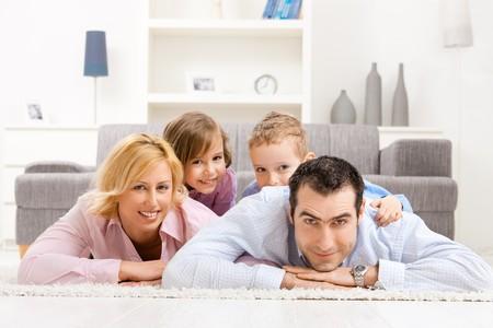 BUEN VIVIR: Familia feliz jugando en casa, acostado colmada piso en la sala de estar.
