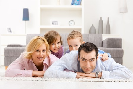 family living: Happy family playing at home, lying heaped on floor in living room. Stock Photo