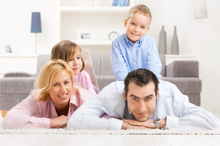 Portrait of happy family lying together on floor in living room, smiling. Stock Photo - 7271534