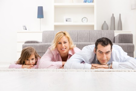 Happy parents and their daugther lying together on floor in living room. photo