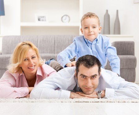 Happy couple and their son lying together on carpet in living room. photo