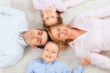 Portrait of happy family lying on carpet with their heads close together, smiling. Stock Photo - 7273426