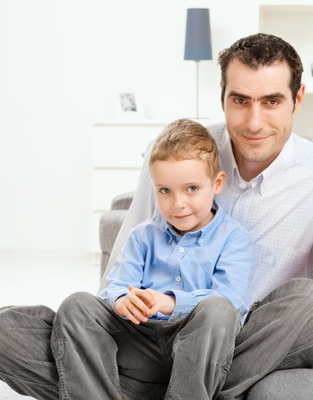 Portrait of father sitting on couch with his son, looking at camera smiling. photo