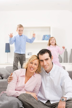 Happy couple sitting at floor at home, embracing. Their children jumping on couch in background. photo
