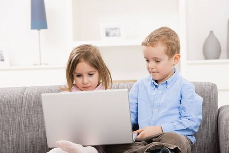 Young children sitting on couch at home, using laptop computer, focusing at screen. photo