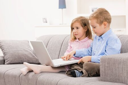 woman couch: Little boy and girls sitting together on couch at home, using laptop computer, looking at screen.