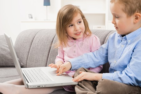 Happy children sitting on couch at home, browsing internet on laptop computer. Girl looking at boy who focusing at screen. photo
