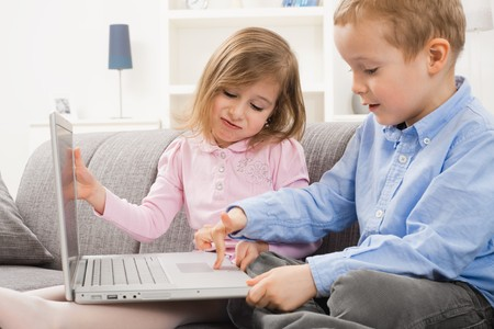 Young children sitting on couch at home with laptop computer. Boy using touch pad, angry girl trying to close teh screen. photo