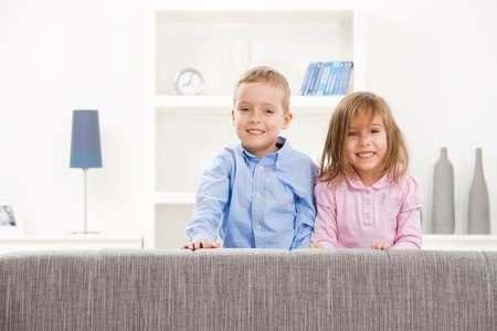 Portrait of happy little siblings sitting together on couch, smiling.  photo