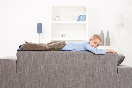 Young boy lying on top of couch at home, looking at camera. photo