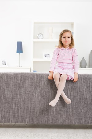 Portrait of 4 years old girl in pink dress, sitting on couch, smiling. photo