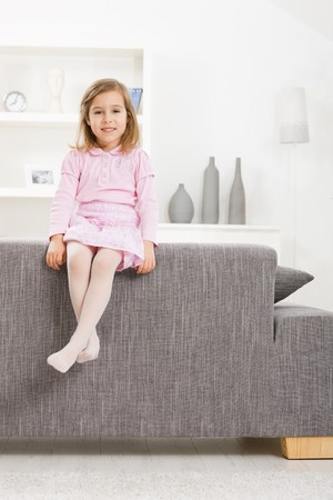 kid sitting: Portrait of happy little girl in pink dress, sitting on couch, smiling. Stock Photo