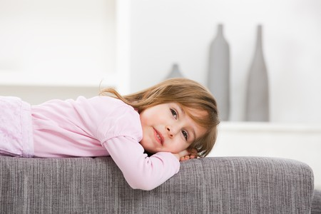 Closeup portrait of happy little girl in pink dress, lying on couch, smiling. photo