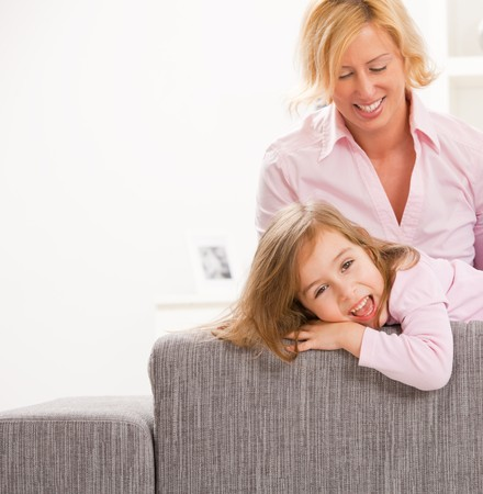 Portrait of blonde little girl and mother wearing pink, laughing happily. photo