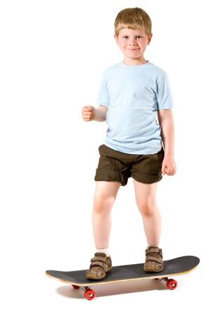 Studio shot of little boy standing on skateboard.  Isolated on white background. photo