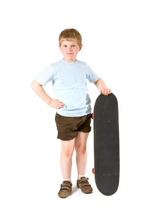 Studio shot of little boy with skateboard.  Isolated on white background. photo