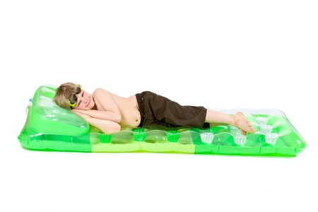 Happy little boy lying on green beach mattress, smiling. Isolated on white. Stock Photo - 7283738