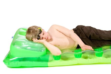 Happy little boy lying on green beach mattress, smiling. Isolated on white. photo
