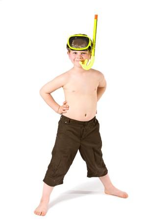 ni�o parado: Chico joven de pie con los brazos en caderas, vistiendo m�scara amarilla y snorkel, sonriendo. Aislados en blanco.