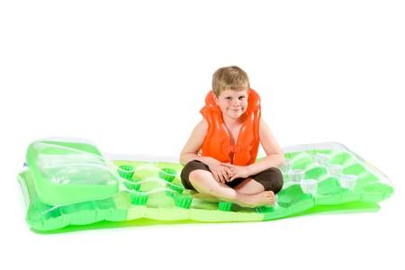 Little boy sitting on green inflatable mattress, wearing orange life vest. Isolated on white. photo