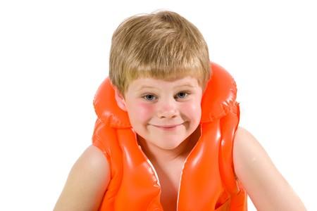 Closeup portrait of little boy wearing orange inflatable life vest, smiling. Isolated on white. photo
