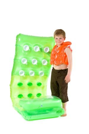 Little boy wearing orange life vest, holding green inflatable mattress. Isolated on white. photo