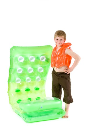 Little boy wearing orange life vest, holding green inflatable mattress. Isolated on white. photo
