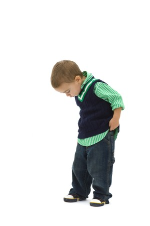 Portrait of preschoold boy posing green shirt and jeans, looking down, isolated on white. photo