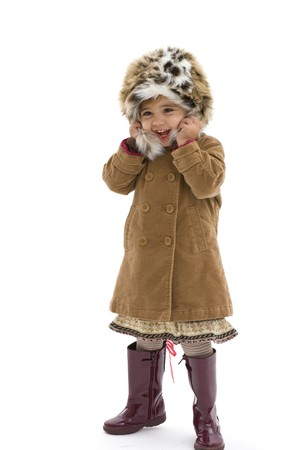 Cute young girl wearing fur hat, brown coat and purple boots. Isolated on white background. photo