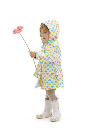 Small girl wearing raincoat and boots, giving pink flower to somebody. Isolated on white background. photo