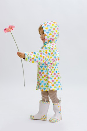 raincoat: Small girl wearing raincoat and boots, giving pink flower to somebody. Isolated on white background. Stock Photo